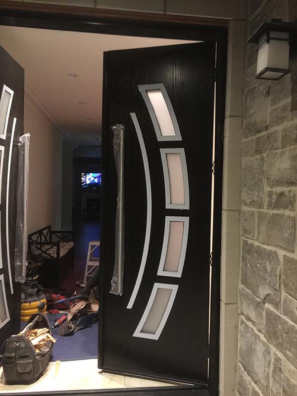 Custom Design Modern Doors with Arched Designed door lites and stainless steel door handles during installation