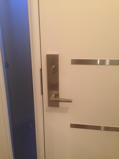 Fiberglass Modern Door with Multi Point Lock and Stainless Steel strips and frosetd side lite installed in Richmond Hill by Modern Doors
