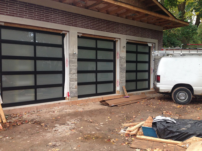 Modern Aluminum Garage Doors with Frosted Door Lites installed in a new modern home in Richmond Hill