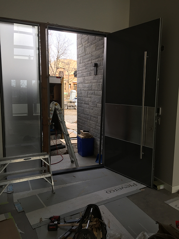 Modern Exterior 10 feet Door with Stainless Steel bar during installation in Vaughan