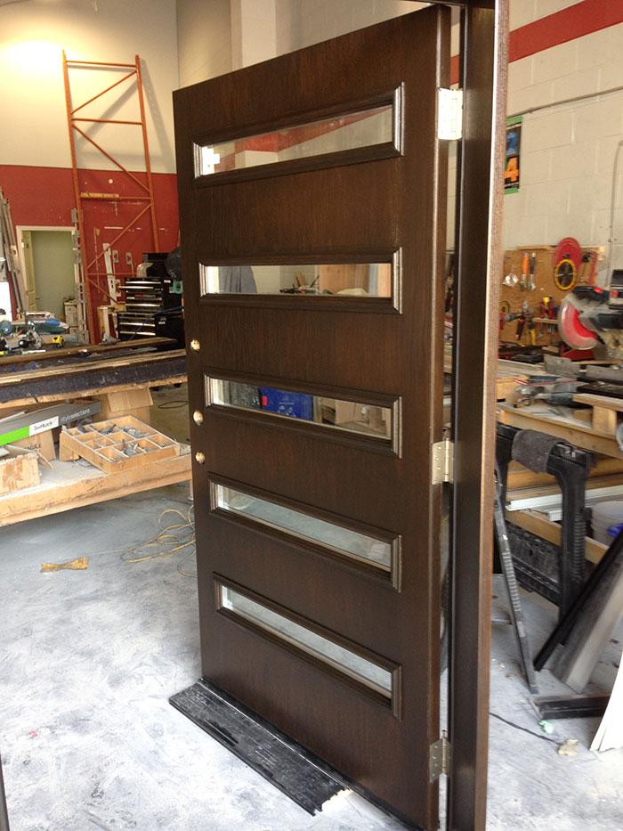 Modern Exterior woodgrain Door with 5 Door Lites and Multi Point Locks During Manufacturing by Giant Doors