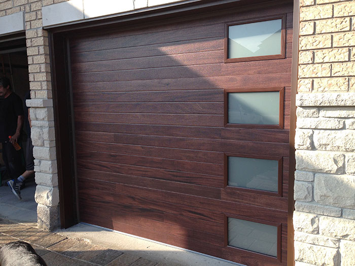 Modern Garage Doors-Fiberglass Modern Double Garage Doors with 4 lites During installation in Oakville-Ontario by modern-doors.ca