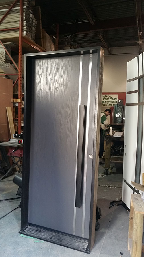 Modern Woodgrain Door with Vertical Stainless Steel Bar and Modern Handle During Manufacturing by Modern Doors