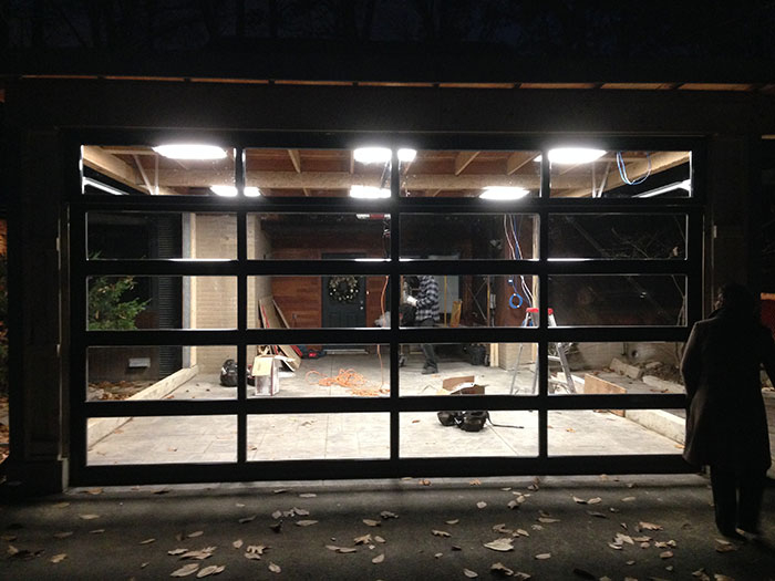 Oversized Aluminum Clear Glass Garage Door DUring The Installation in Custom Home in Oakville by Modern Doors