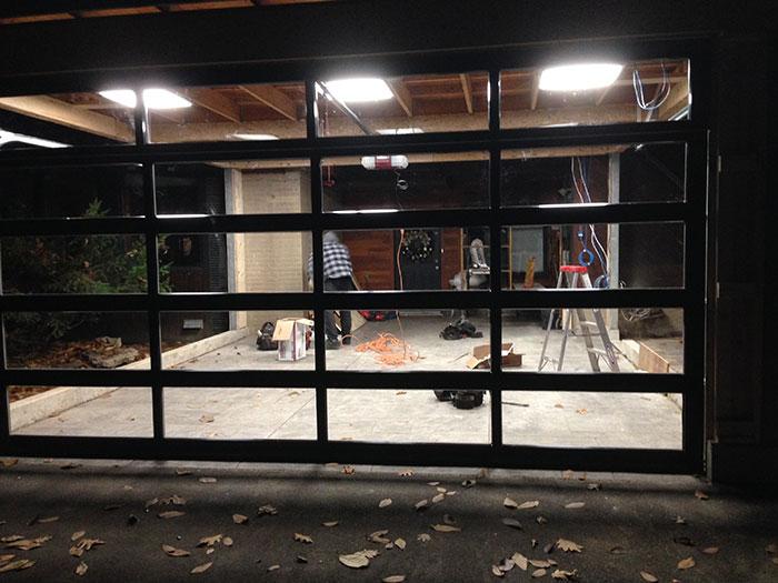 Oversized Aluminum Glass Clear Garage Door During Installation in Custom Home in Oakville by modern-doors.ca